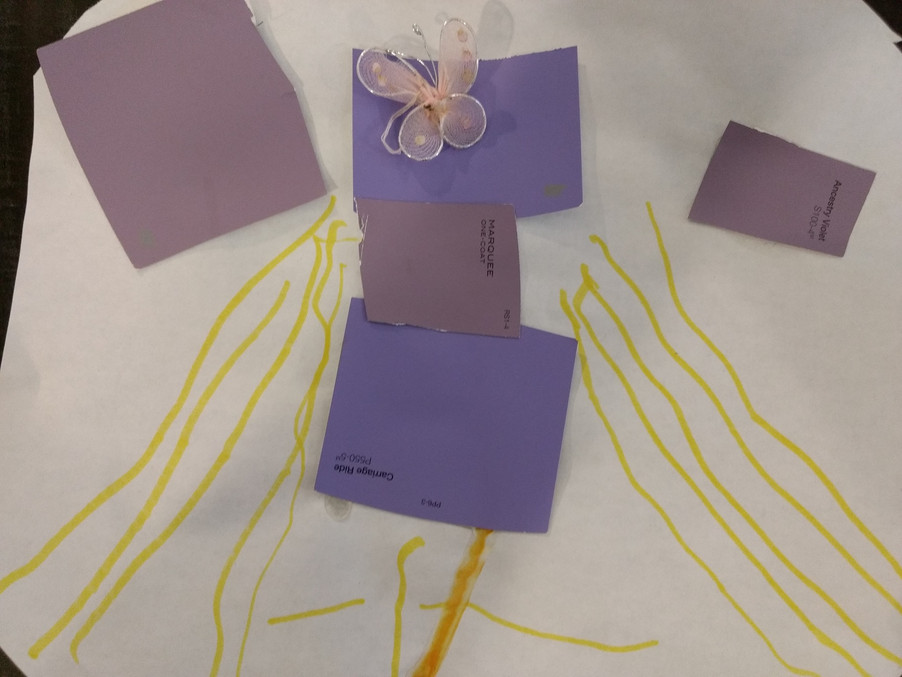 Child artwork with purple squares glued to white paper, yellow lines drawn, and pink lace butterfly