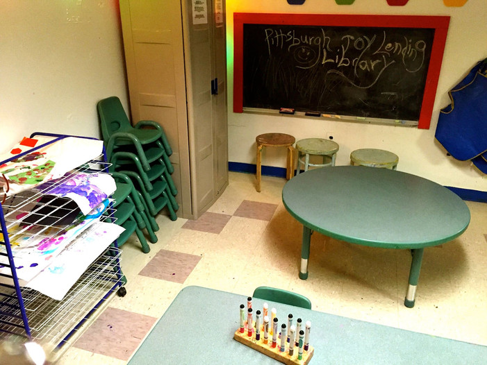 Art room, with cabinet, tables, chairs, drying rack, and chalkboard