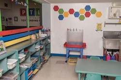 PTLL art room, with easel against wall and shelves of art materials