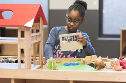 Child playing with wooden dollhouse with furtniture and dolls
