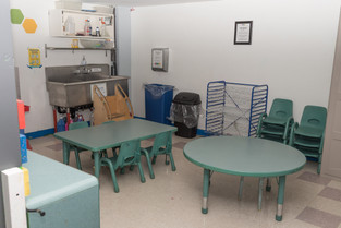 Art room, with tables, chairs, drying rack, and sink
