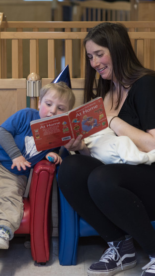 Parent sitting on small blue chair, smiling, nursing baby and reading book to older child