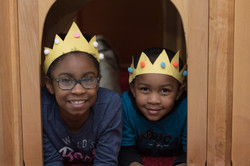 Two children wearing crowns, lying inside toy house, look at camera and smile