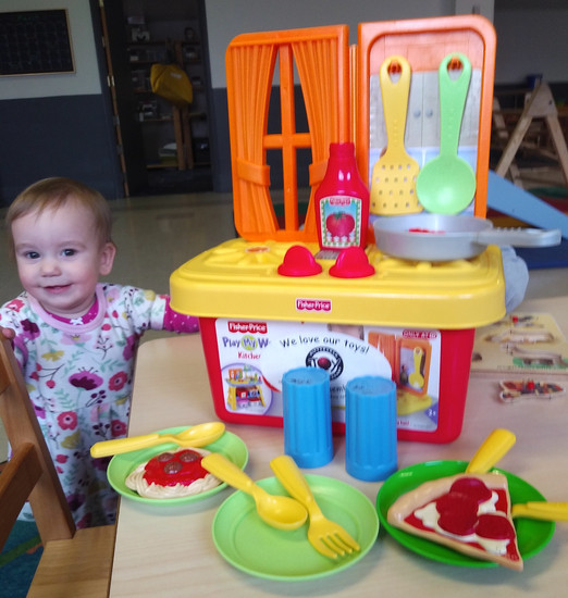 Baby smiles at camera next to play set of tabletop kitchen