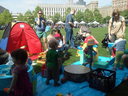 Outside at event, adults and children stand on/near a blue blanket in grass, playing with toys