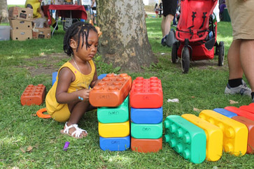 Child kneels in grass to play with large building bricks