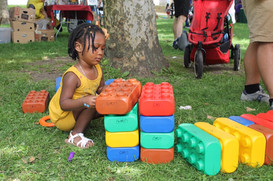 Child squats in grass, looking down while building with giant blocks