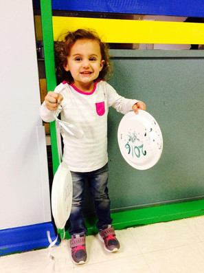 Inside PTLL, child looks at camera and smiles, holding two paper plates, one of which reads 2016
