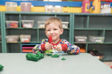 Art room, child smiles at camera, holding play-dough scissors with play-dough on table in front