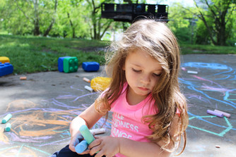 Child sits outdoors, looking down, holding two pieces of sidewalk chalk