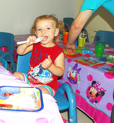 Toddler sits at table with Disney table cover, holds plastic fork to mouth