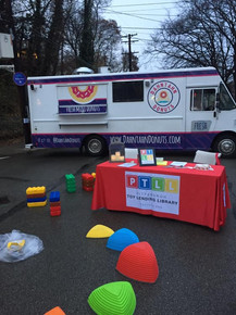 PTLL event table with Gonge riverstones and large building blocks nearby, in front of food truck