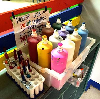 Art room, close-up of large paint bottles next to bin with paintbrushes