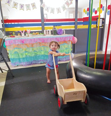 Happy birthday banner and ruffled table skirt behind toddler who pushes wooden cart
