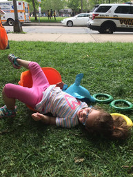 Child lying in grass on top of and near ring toss toys