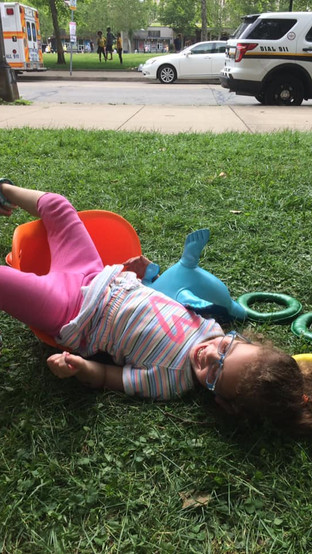 Child lying in grass outside, laughing, on top of and near tossing ring toys