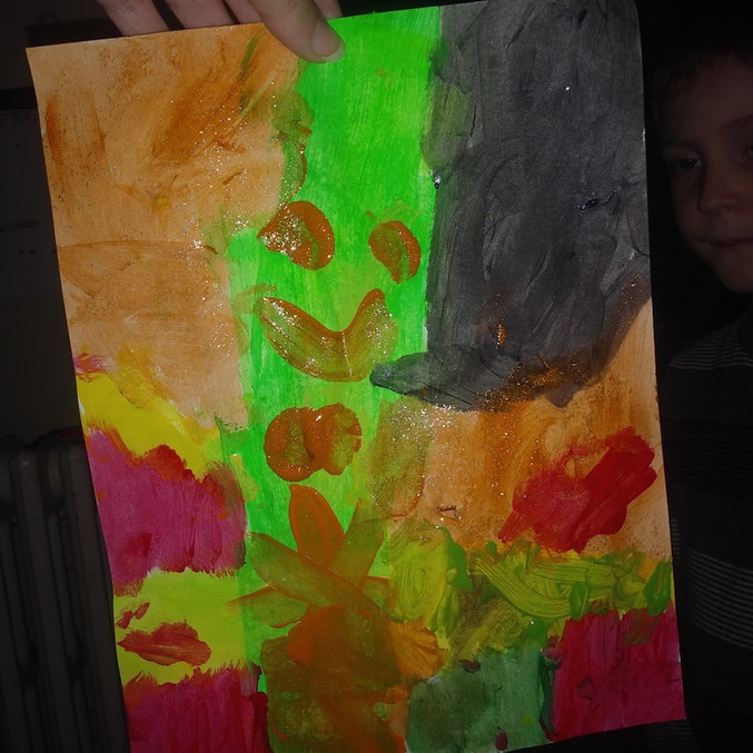 Child's painting, covering whole page, orange/black/red, with green in middle with red smiley face