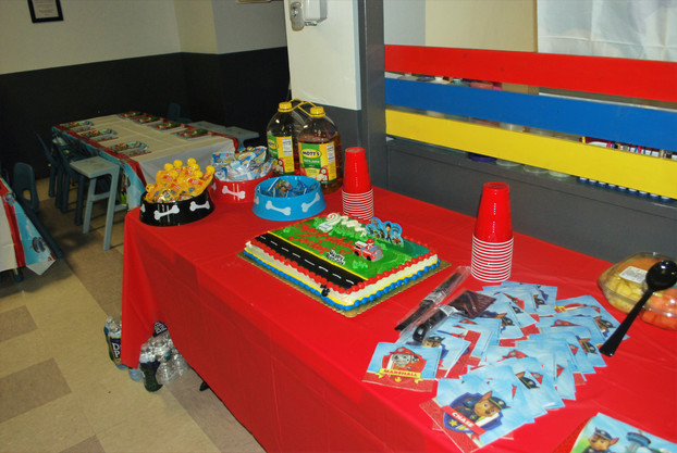 Table set up with red table cover, snacks, drinks, Paw Patrol cake
