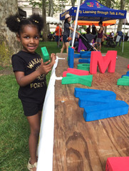 Child smiles at camera, holding large foam letter, next to our event table with other letters