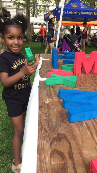 Child outdoors at event table, with large foam letters, looking at camera, and smiling