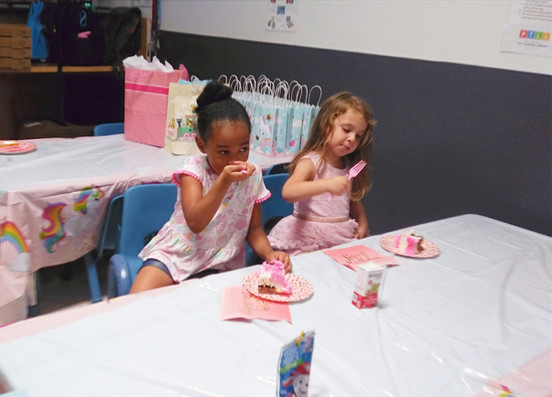 Two children sit at front tables with pink/white table cover, eating cake
