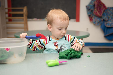 Child in PTLL art room, at table looking at play-dough, a cutting tool in one hand raised above it