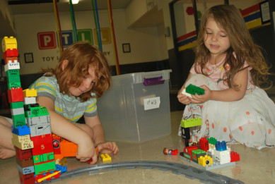 Two children sit on floor, looking down, playing with Thomas Duplo train set