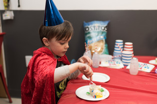 Child with party hat and cape sits at table, looking down and putting fork into cake