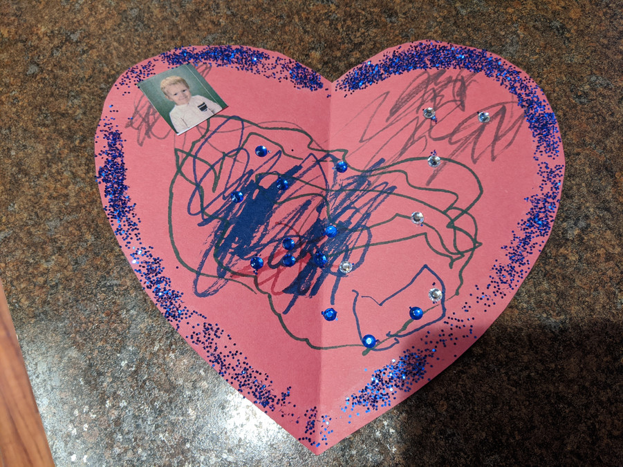Pink paper heart, with blue glitter, squiggly lines drawn in blue, and child's photo glued to top