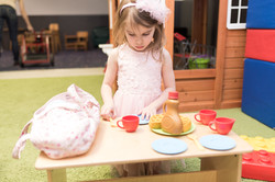 PTLL interior, child stands at play table, looking down at play food, plates, and cups