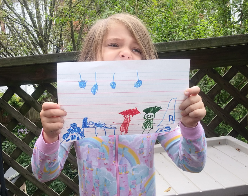 Child standing outside, holding drawing of one red, one green person standing by blue person on bed