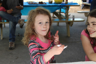 Child mid-bite of cake, holding fork, looks at camera. Child to the right, half out of frame, laughs