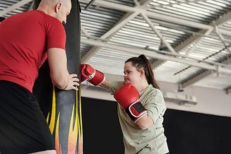 Eine Frau mit Trisomie21 boxt. Der Trainer unterstützt sie.