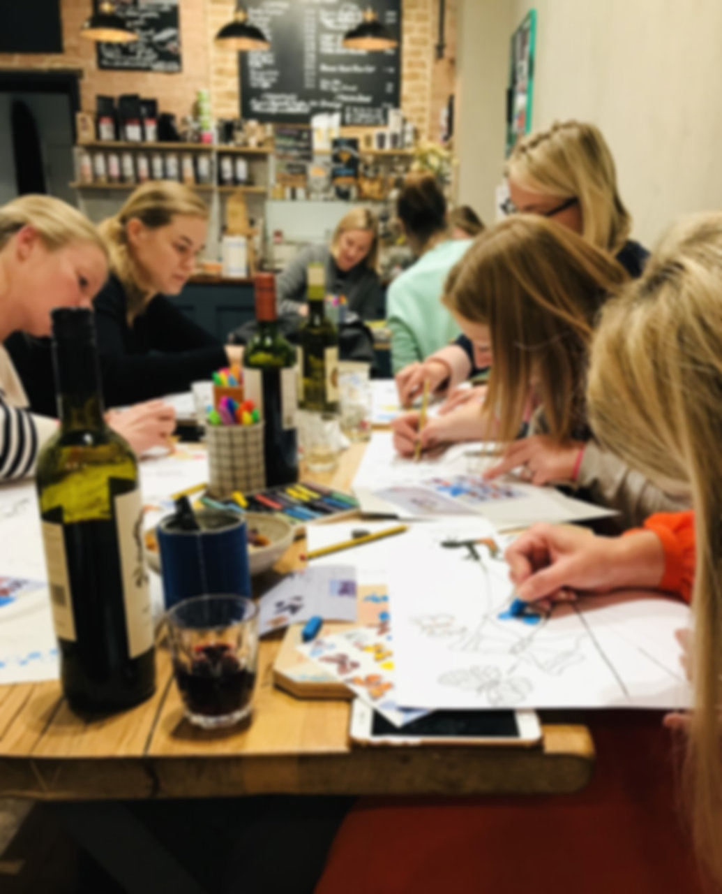 Women sitting at a table with glasses of wine, sketching and colouring