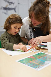 Young child getting help from Celia to add elements to her artwork