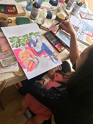 Woman holding a baby on her lap as she works on her watercolour painting