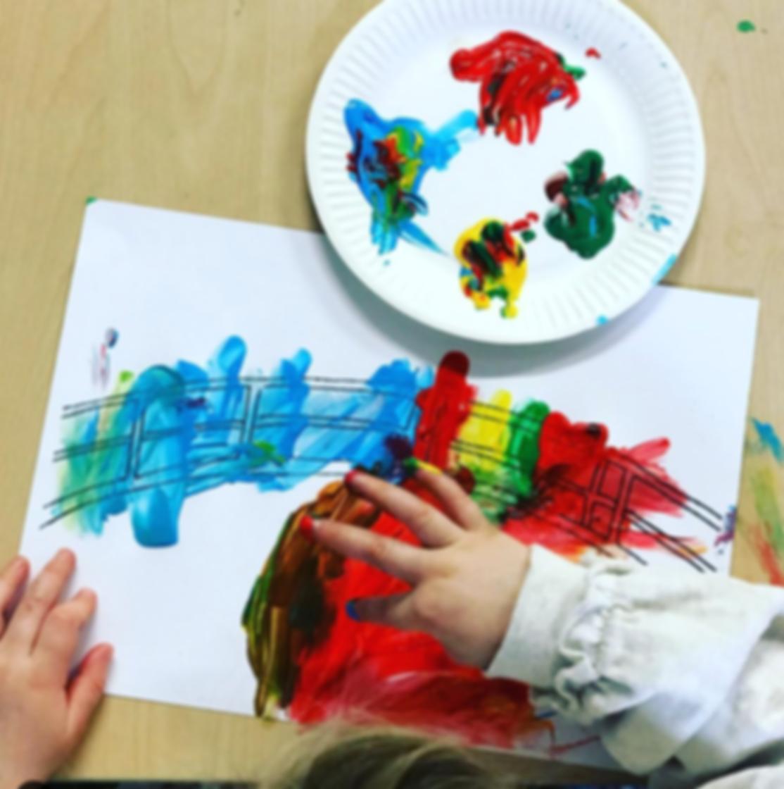 child hands finger painting a bridge