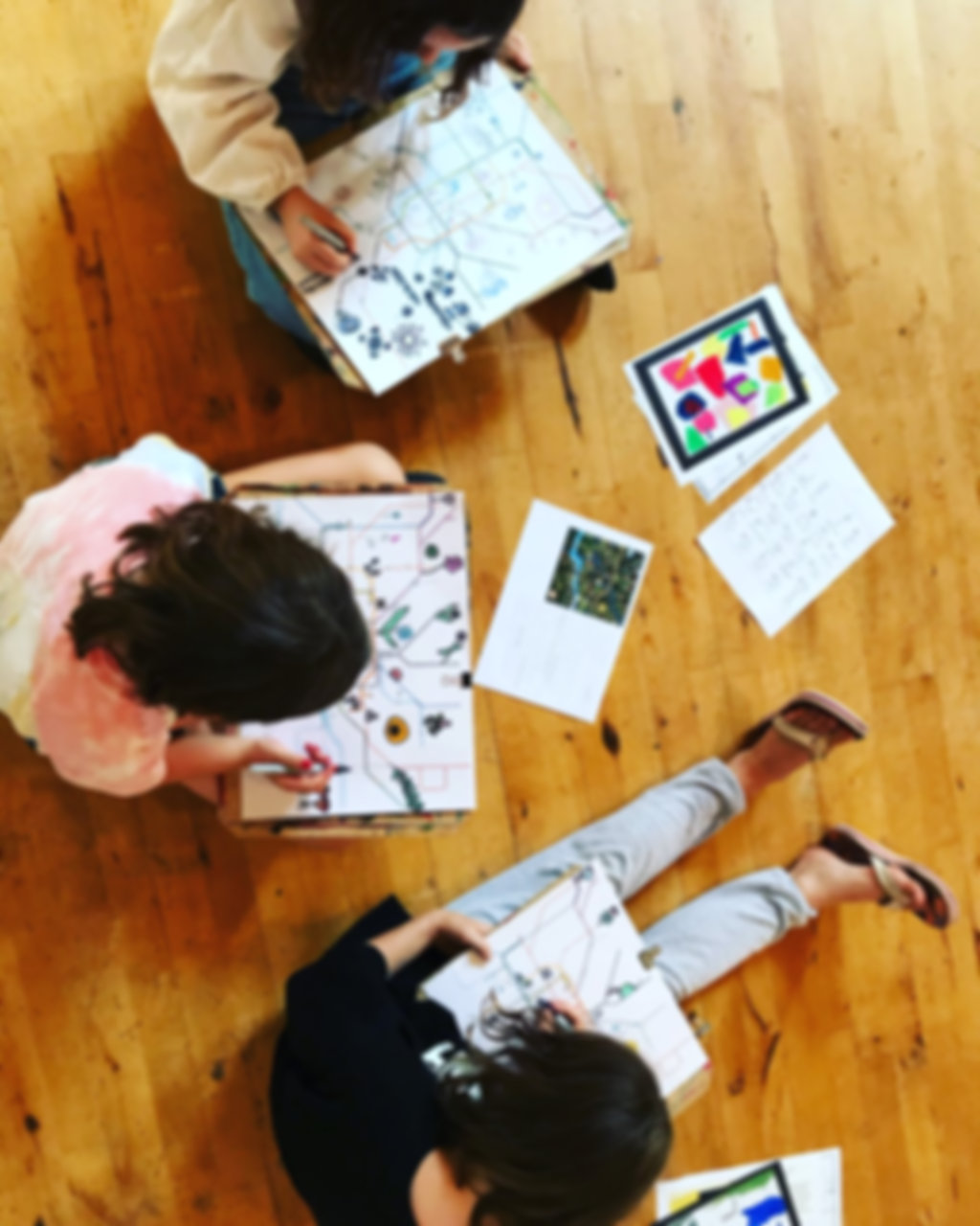 Overhead view of children sitting on the floor drawing with markers
