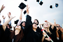 group-of-diverse-grads-throwing-caps-up-
