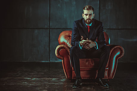 Young handsome businessman with beard in black suit sitting on chair and talking with speaker. Film
