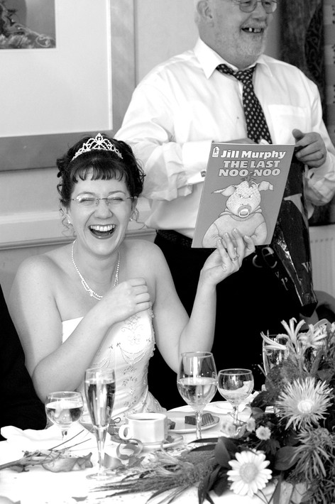 Bride with book during wedding reception, Sheffield