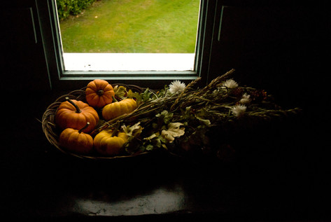Basket of decorative gourds on window sill
