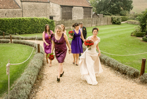 Bride walking with bridesmaids at Priston Mill, Bristol