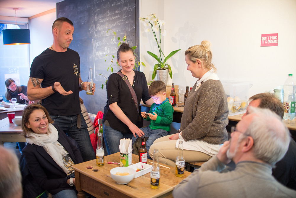 Group of people and child around a table at Cafe Gratitude during Rempah's party.