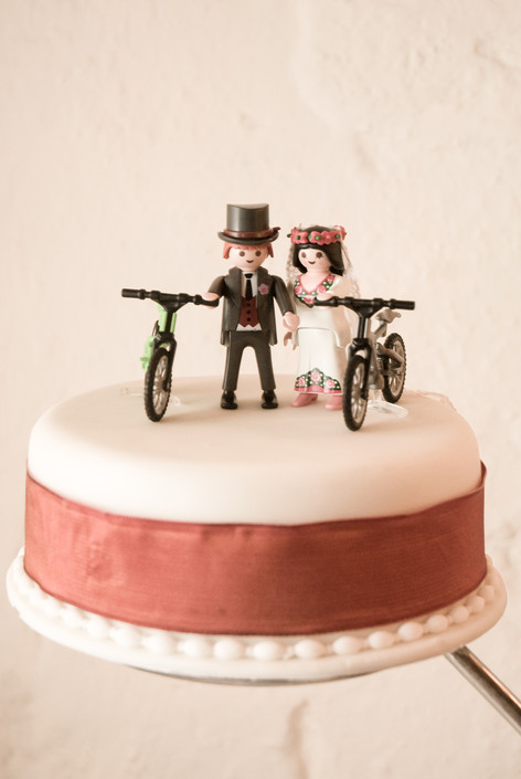Playmobil figures with bikes on top of wedding cake