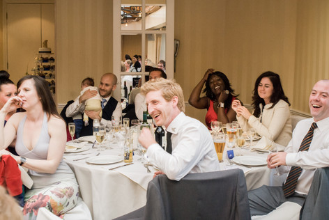 Guests listening to speeches during wedding reception at Hampton Court Mitre Hotel