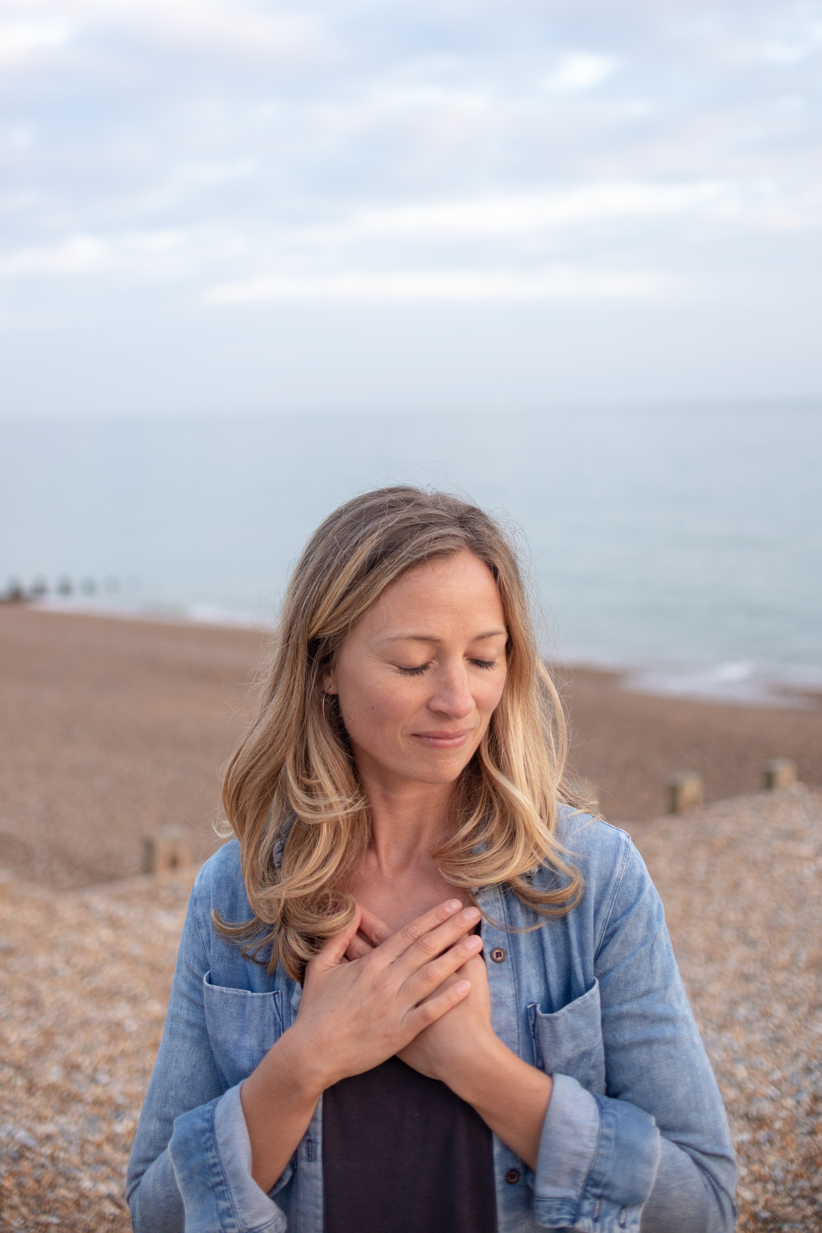 Yoga teacher Brea with hands on heart in front of sea