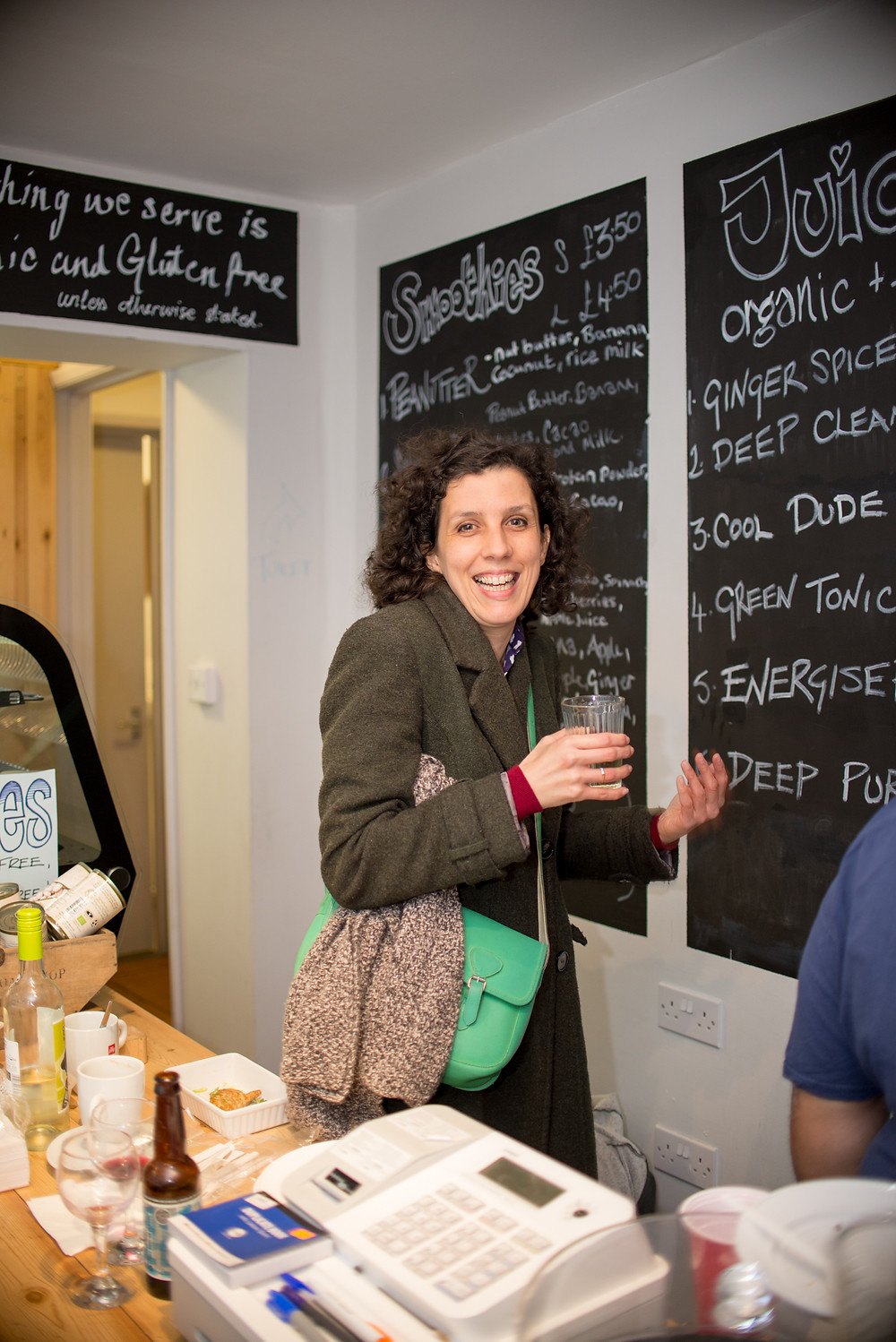 Smiling lady with drink at Cafe Gratitude during Rempah's party.