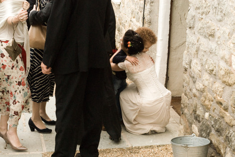 Bride hugging young guest at Priston Mill, Bristol
