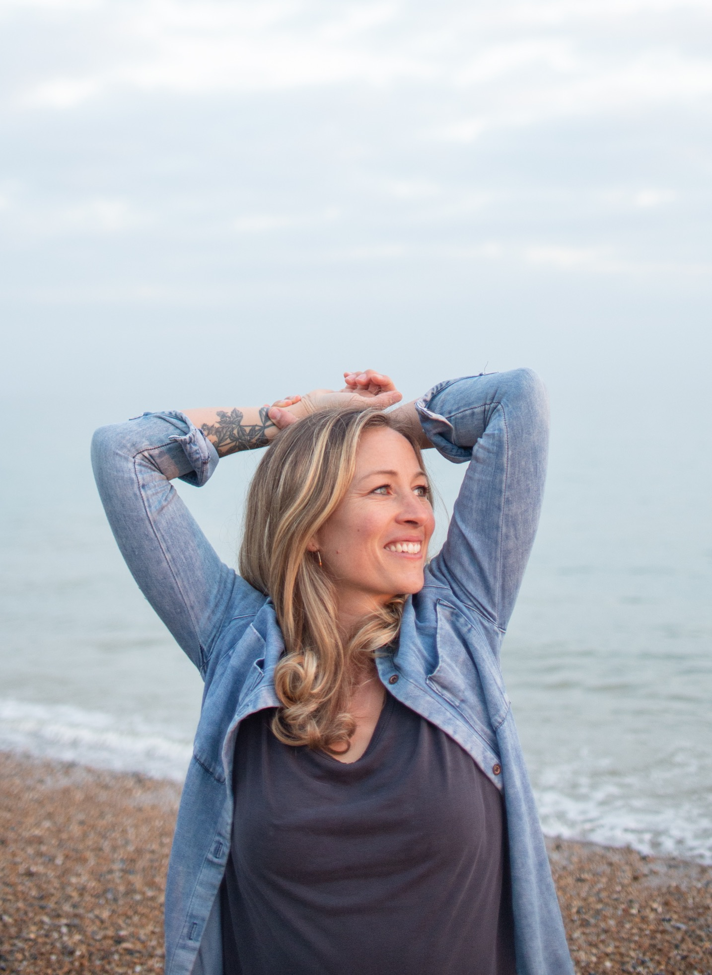 Yoga teacher Brea smiling with hands on head in front of sea